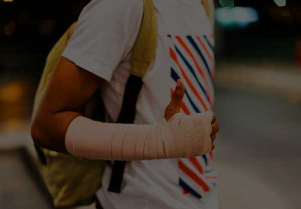 Person with forearm and hand bandaged giving the thumbs up sign